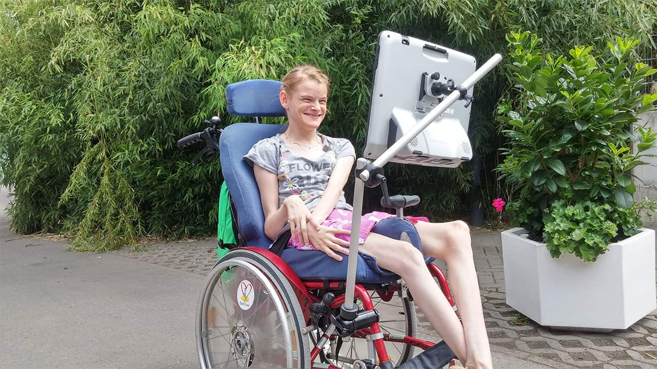 Nele uses Rehadapt's modular wheelchair mounts for her AAC device